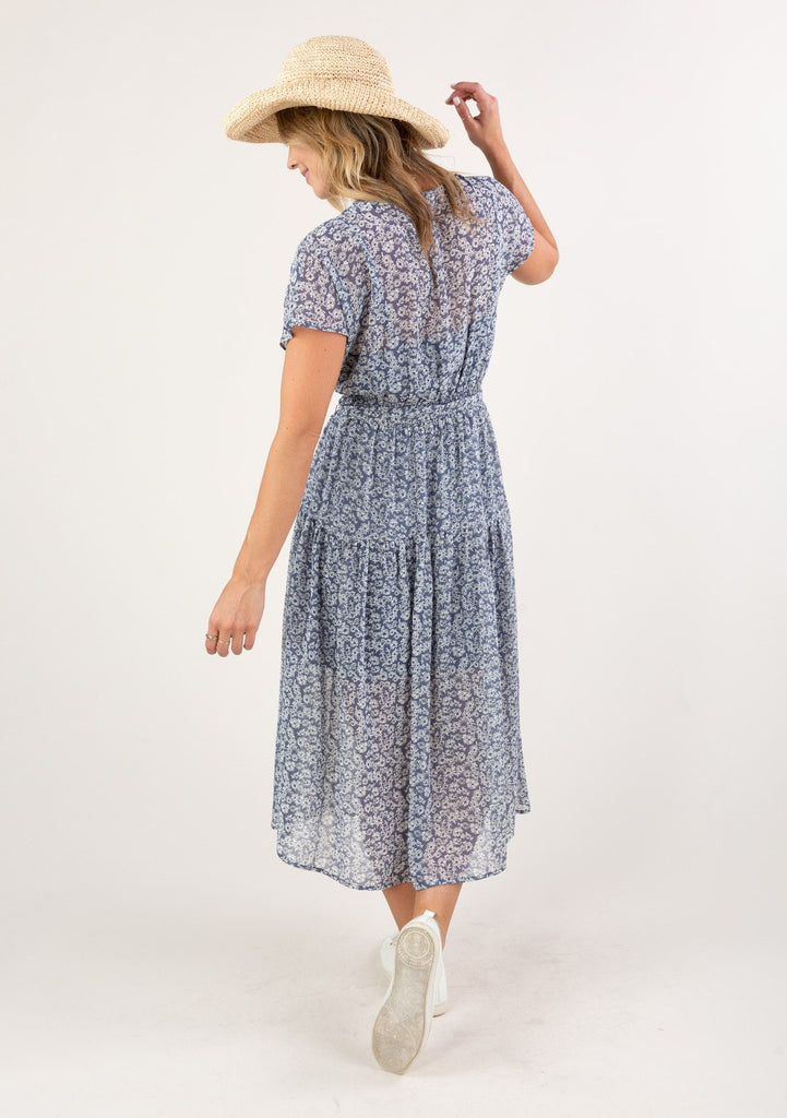 [Color: Denim Ivory] A brunette woman standing outside wearing a gorgeous seventies inspired floral ditsy midi dress. The slimming belted waist and v neckline accentuate your curves.