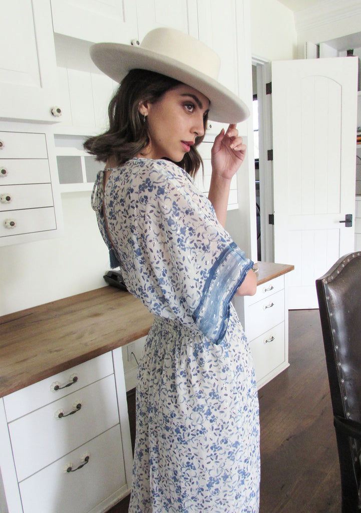 [Color: Blue/Ivory] A brunette woman standing inside wearing a Lovestitch blue and ivory floral printed, kimono sleeve maxi dress with smocked waist and tie back open detail.