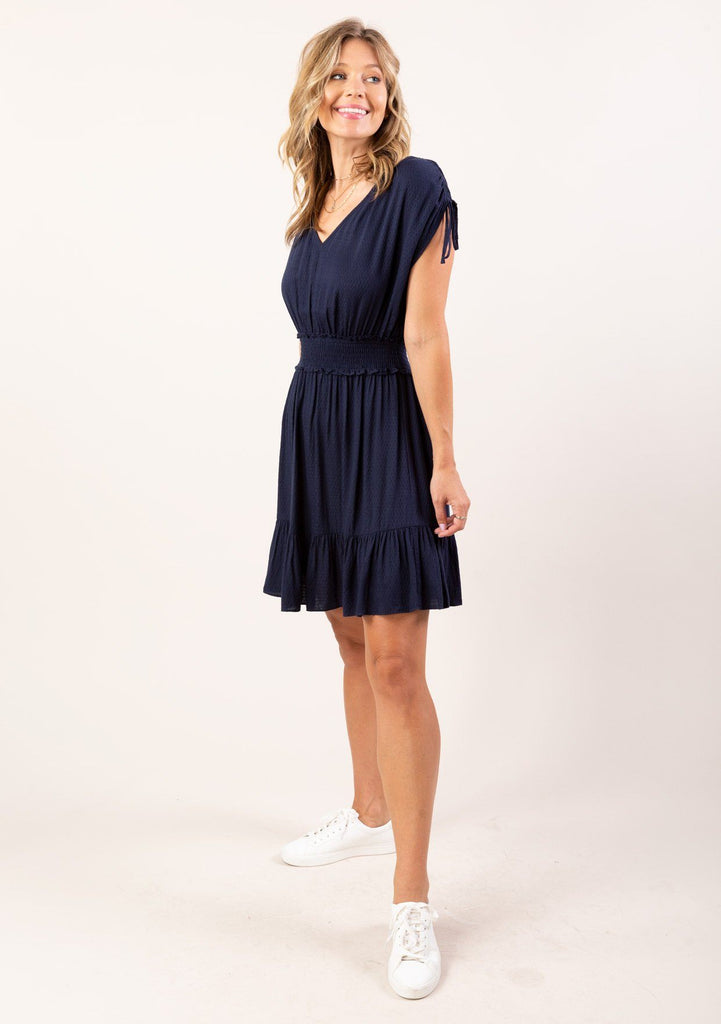 [Color: Navy] Keep it short and sweet in our adorable mini dress in a textured jacquard. Featuring a trendy ruched drawstring shoulder detail, a smocked elastic waist for definition, and a flirty tiered skirt with ruffle details. A versatile mini dress for work or play.