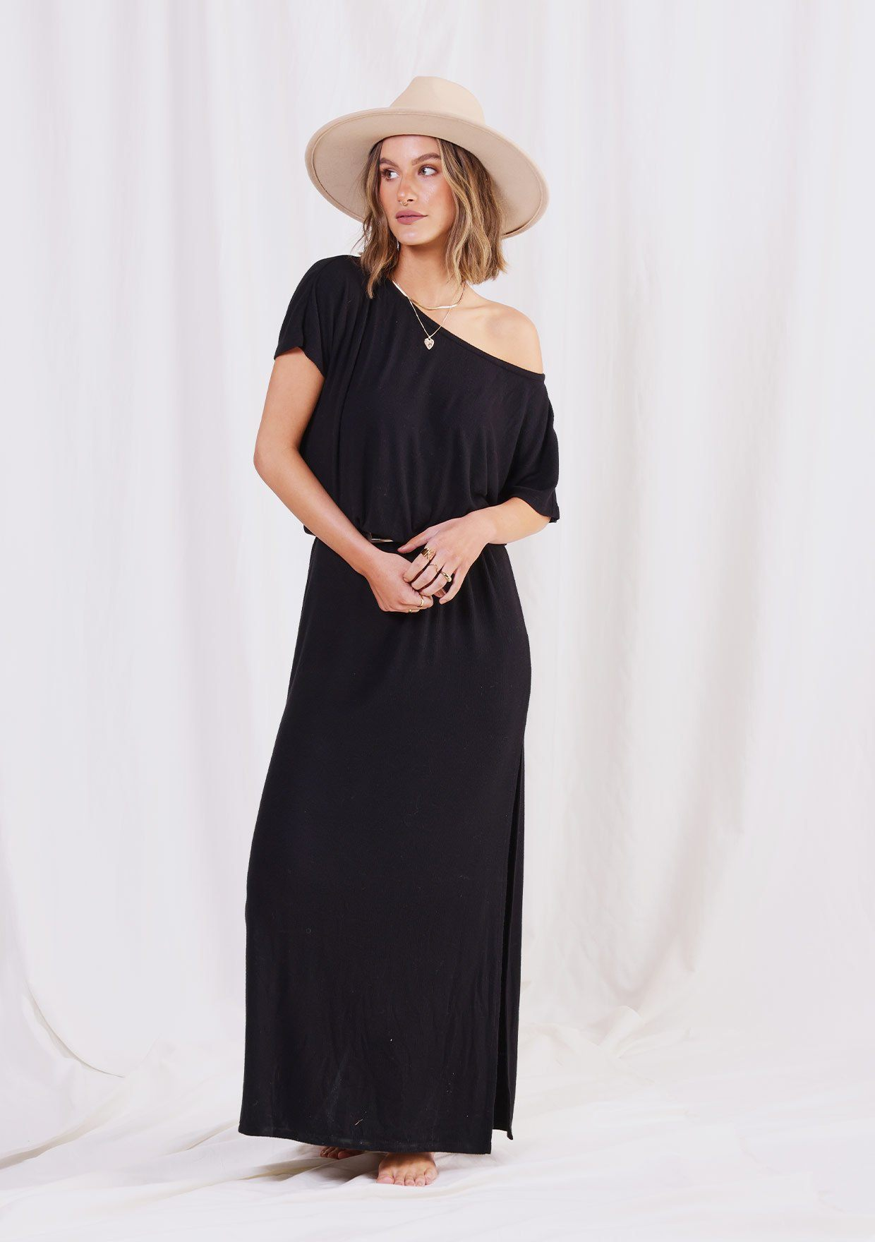 [Color: Black] A woman standing against a white back drop wearing a soft micro ribbed maxi dress with an elastic waist, short sleeves, and a wide neckline that can be worn off the shoulder.