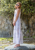 [Color: Blush/Blue] A woman on the beach wearing a sheer sleeveless maxi dress in a watercolor print. Featuring a button front, a v neckline, and a tiered skirt. Slip included.