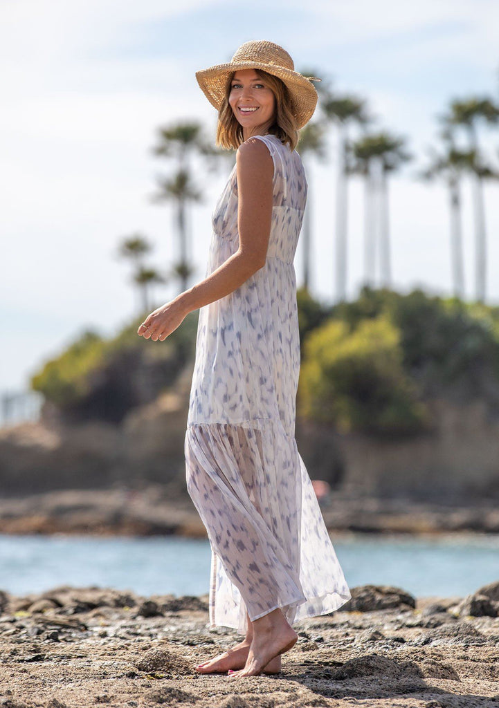 [Color: Off White/Grey] A woman on the beach wearing a sheer sleeveless maxi dress in a watercolor print. Featuring a button front, a v neckline, and a tiered skirt. Slip included.