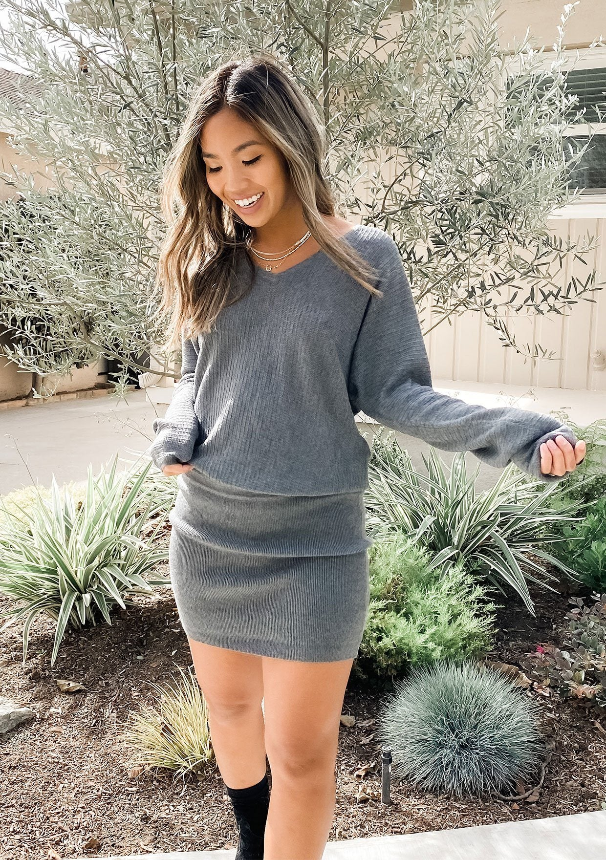 [Color: Heather Charcoal] Soft blouson mini sweater dress. Featuring a loose fitting bust, a fitted banded skirt, and a flattering v neckline. Styled here with boots.