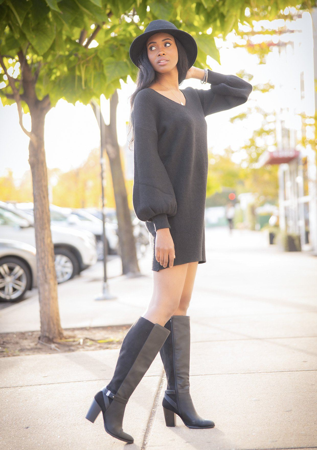 [Color: Black] A super soft ribbed sweater dress. A voluminous lantern sleeve and v neckline add interest to this warm and comfortable style. Styled here with knee high boots.