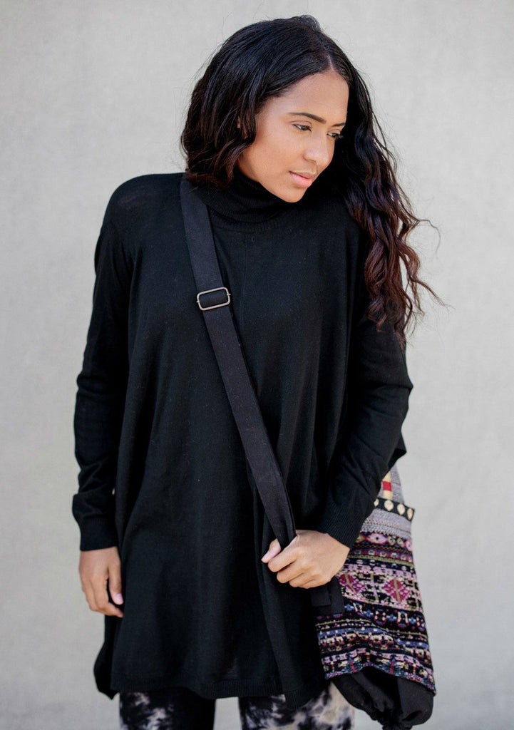 [Color: Black] A turtleneck sweater poncho featuring a flattering draped silhouette, breezy side vents, and a slightly longer tunic style length. Paired here with joggers and a yoga bag.
