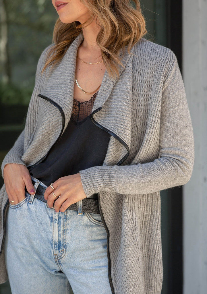 [Color: Heather Grey] A blond woman wearing a cozy ribbed cardigan. Featuring a faux leather trim, a draped shawl collar, and an open front.