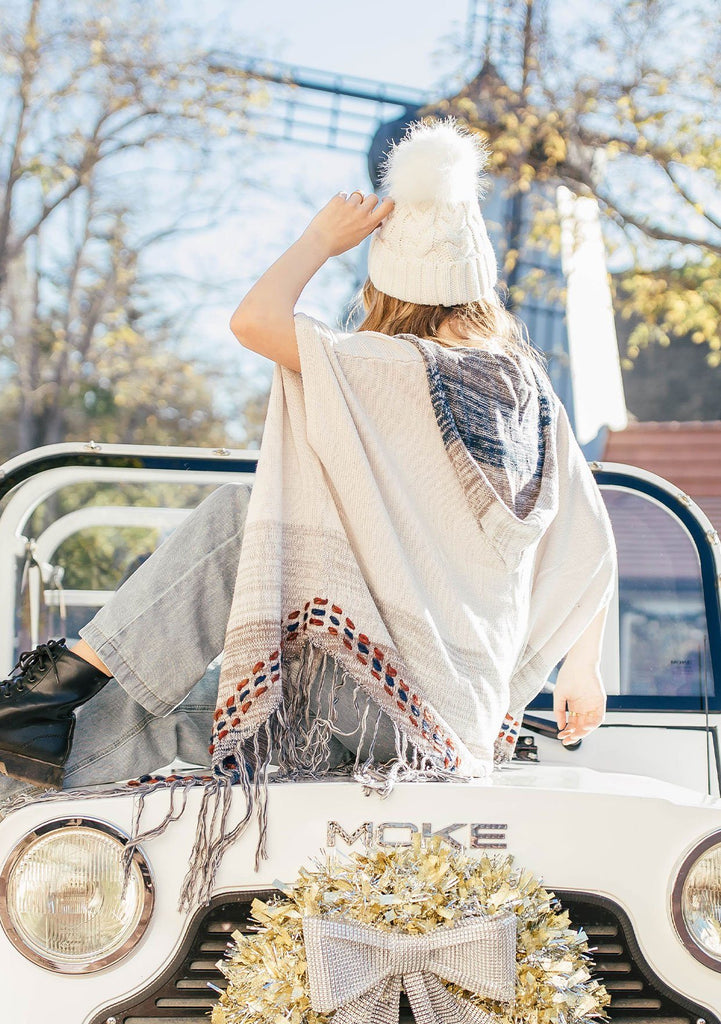 [Color: Sand/Grey] A blond woman wearing a lightweight hooded poncho. Featuring a fringed asymmetric hemline, an oversize hood, and a multi color striped pattern.