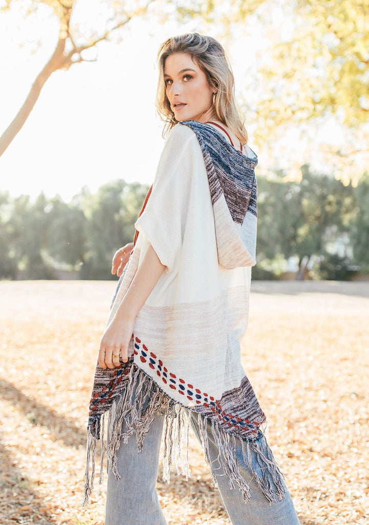 [Color: Off White/Beige] A blond woman wearing a lightweight hooded poncho. Featuring a fringed asymmetric hemline, an oversize hood, and a multi color striped pattern.