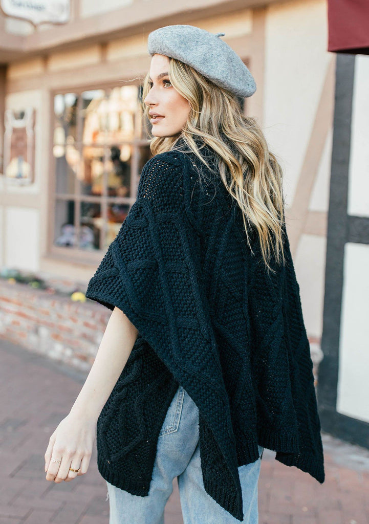 [Color: Black] A blond woman outside wearing an ultra soft chunky cable knit poncho sweater. Featuring a cozy cowl neckline.