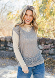 [Color: Light Grey] A woman outside wearing a vintage inspired crochet vest. Featuring a flattering v neckline, a relaxed and easy fit, and a crochet open knit front.