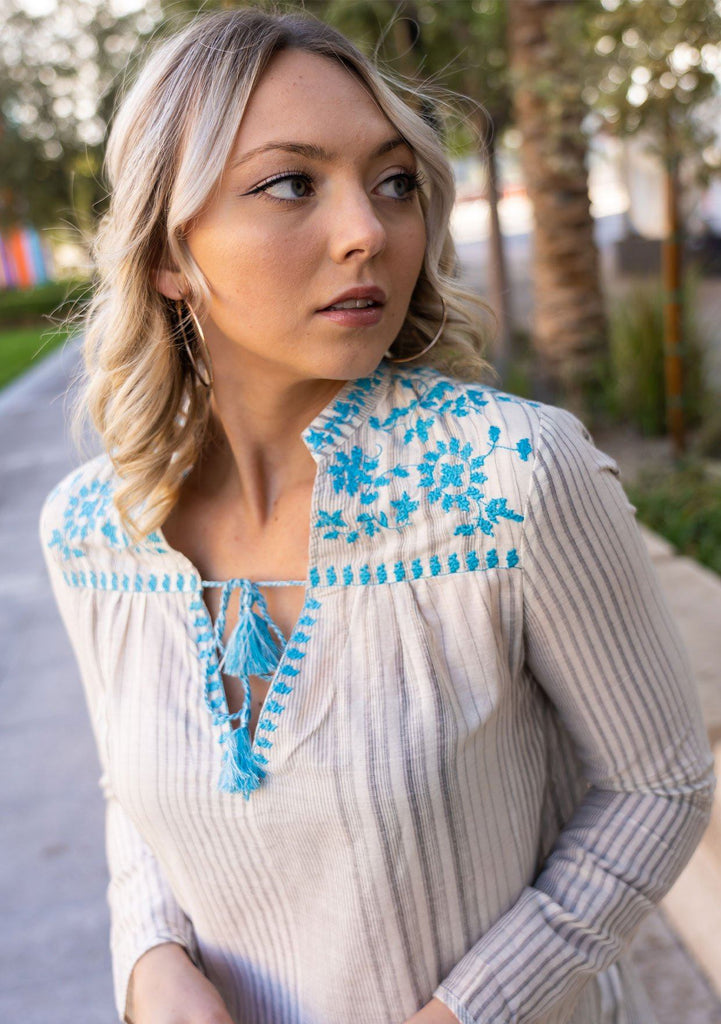 [Color: Turquoise] A blond woman wearing a cotton embroidered blouse. Featuring a split neckline with tassel tie accents and a floral embroidered yoke detail.