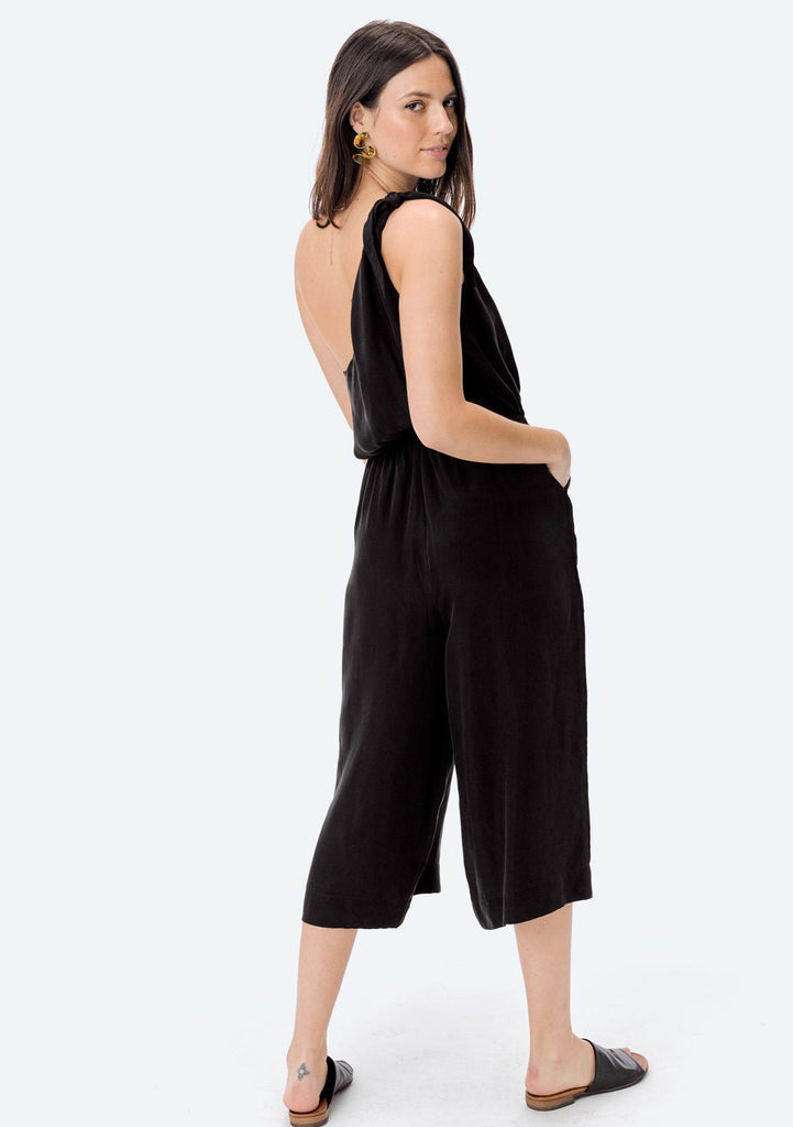 [Color: Black] Shop Lovestitch bohemian chic one shoulder jumpsuit with flattering cropped wide gaucho legs and pockets.