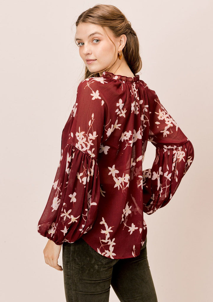 [Color: Brick/Rosewater] A bohemian blouse in a pretty floral print. Featuring elegant and flattering voluminous lantern sleeves, a split neckline with tassel ties, and flirty ruffle details.