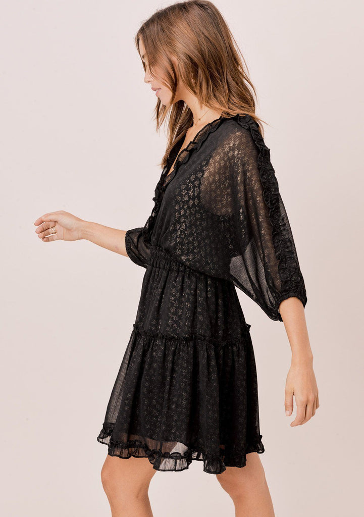 [Color: Black/Gold] A foil chiffon mini dress, featuring a ruffle trimmed v neckline in front and back, ruffle trimmed three quarter length sleeves, and a tiered skirt.