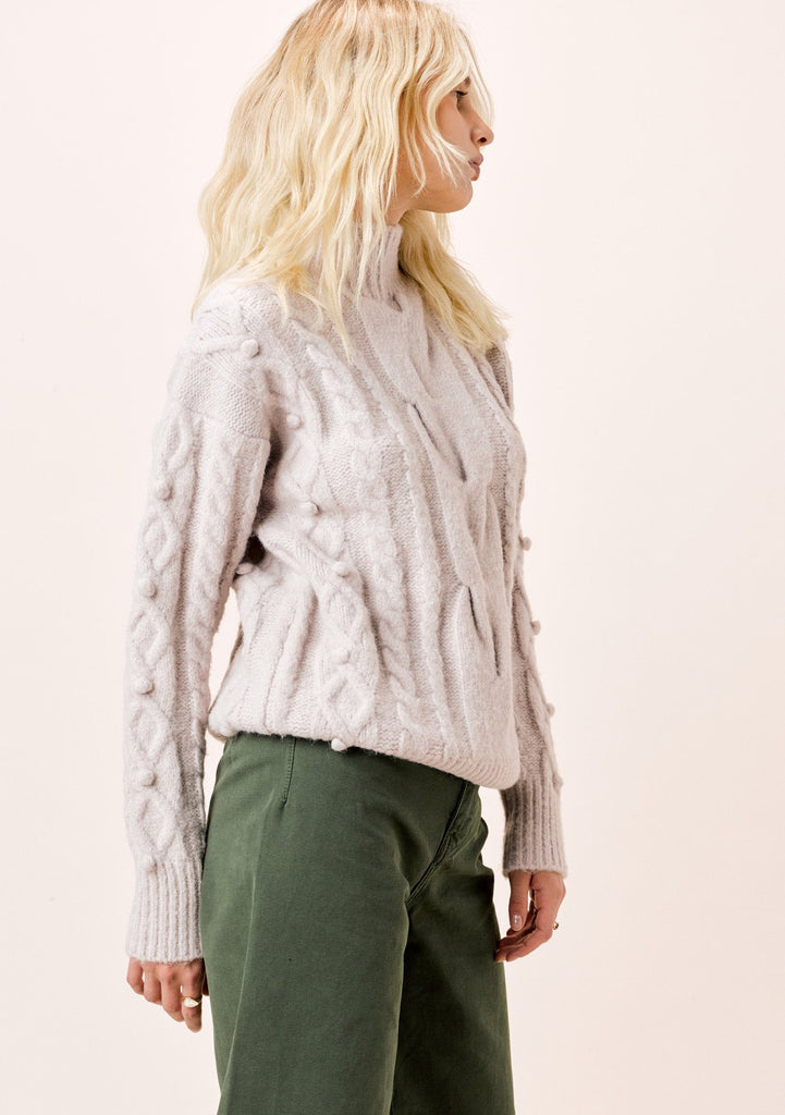 [Color: Light Taupe] Long sleeve, light taupe, cable knit, mock neck sweater with pom-pom details.