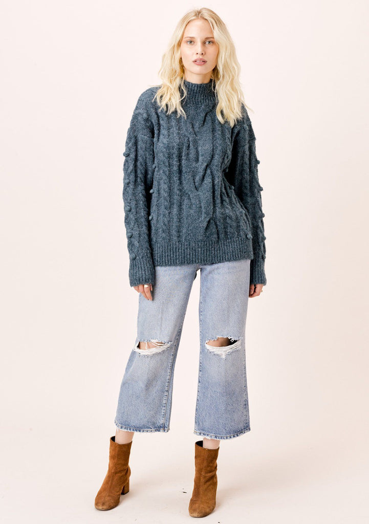 [Color: Teal] Long sleeve, teal blue, cable knit, mock neck sweater with pom-pom details.