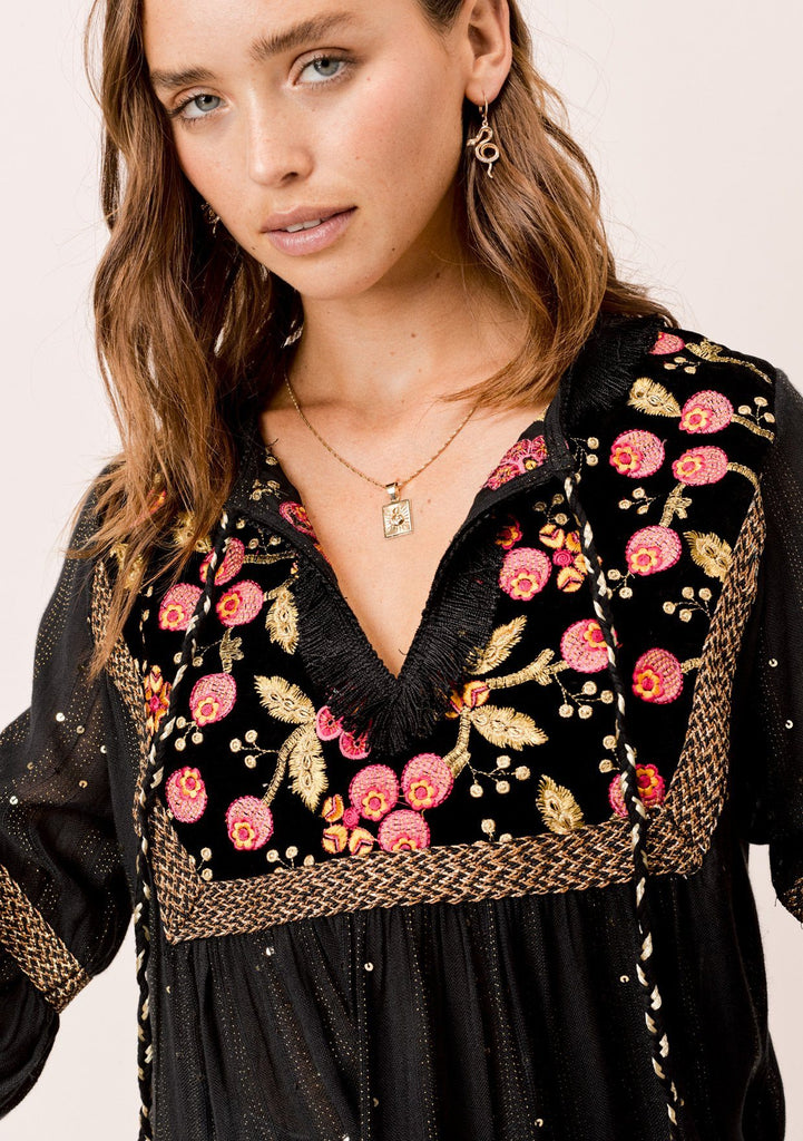 [Color: Black/Multi] Lovestitch black embroidered bib front, lantern sleeve top with metallic trim detail and tassel tie neck.