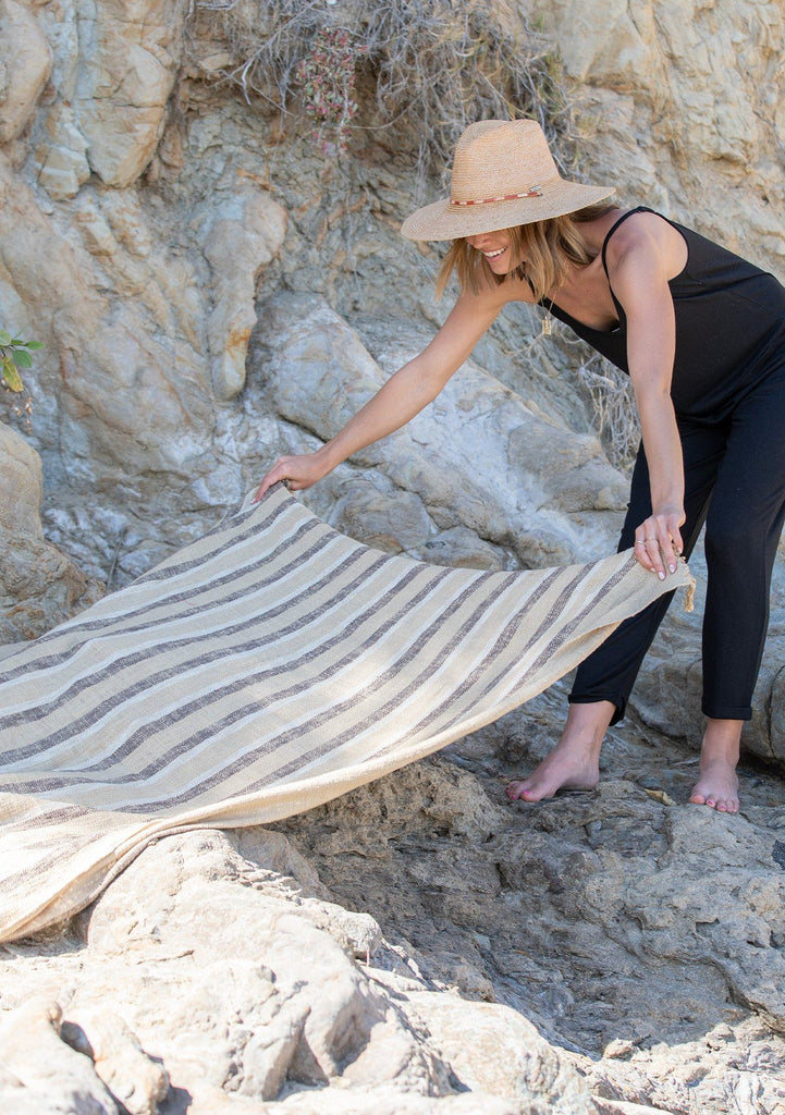 [Color: Beige/Brown] A woman outside on the beach placing a beige and brown striped beach throw. Featuring a fringed hem and a washed stripe throughout.