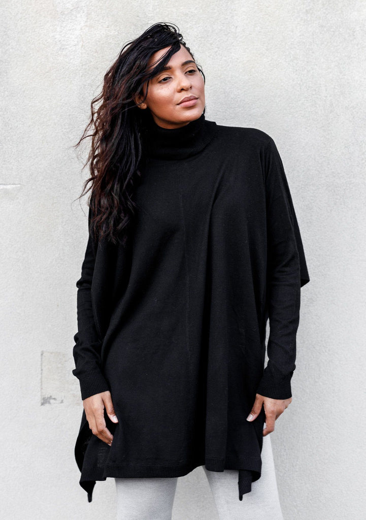 [Color: Black] A woman standing outside wearing a turtleneck sweater poncho. Featuring a flattering draped silhouette, breezy side vents, and a slightly longer tunic style length.