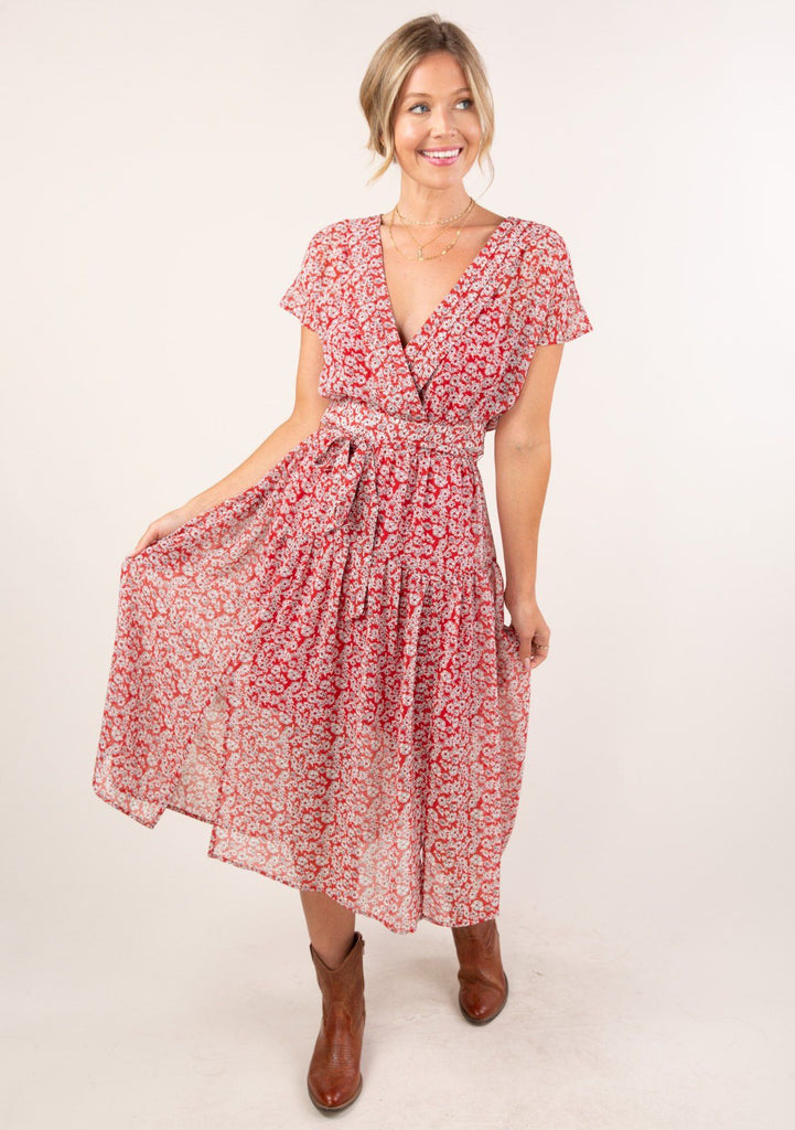 [Color: Red Ivory] A brunette woman standing outside wearing a gorgeous seventies inspired floral ditsy midi dress. The slimming belted waist and v neckline accentuate your curves.