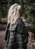 [Color: Black/Grey] Wrap yourself up in this cozy, oversized plaid scarf wrap with mini fringe trim. A classic style that pairs effortlessly with everything.