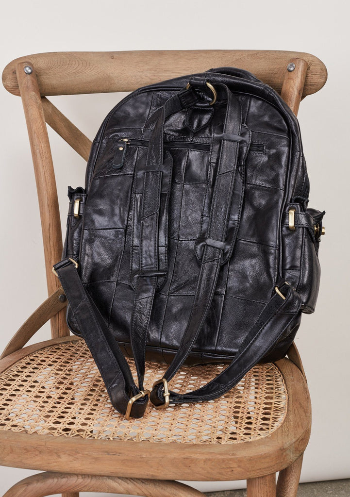 [Color: Black] Patchwork leather backpack with top handle and multiple outer pockets.