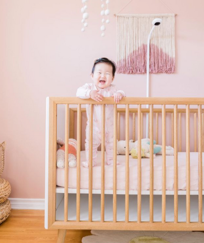 Nora in her crib in her soft pink nursery