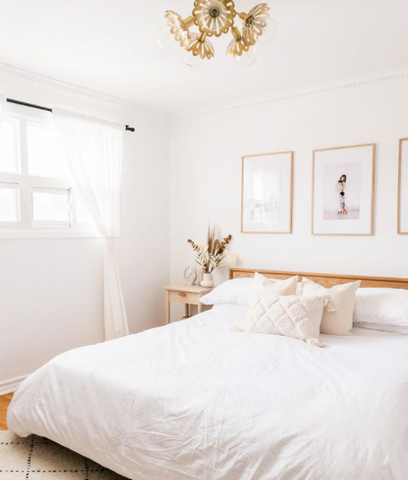 A beautiful bedroom with white linen and framed photos