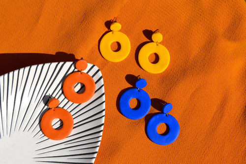 A selection of Handmade bold colourful blue, yellow and orange circle earrings.