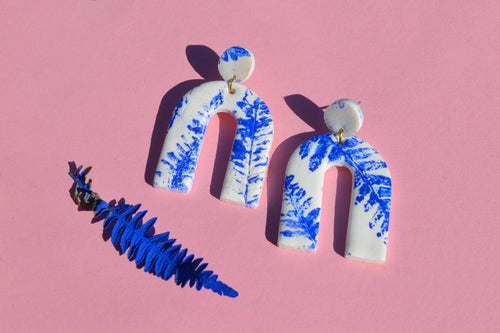 Blue pressed fern leaf on white arch clay earrings. FREE WORLD SHIPPING on orders over £30. Handcrafted by British fashion designer Sophie Filomena.