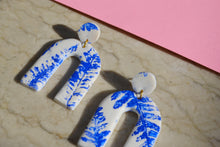 Load image into Gallery viewer, Blue pressed fern leaf on white arch clay earrings. FREE WORLD SHIPPING on orders over £30. Handcrafted by British fashion designer Sophie Filomena.