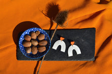 Load image into Gallery viewer, Simple white arch with orange halfmoon stud, made in Bristol UK by Sophie Filomena. Bowl of Nutmeg on stone slate with dried teasel plant.