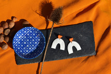 Load image into Gallery viewer, Simple white arch with orange halfmoon stud, made in Bristol UK by Sophie Filomena. Blue bowl, Nutmeg spilling out, with dried teasel flower places on slab.