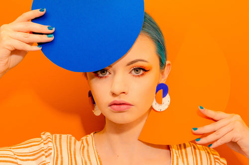 Buy alternative jewellery. Girl with blue hair, holding abstract blue and orange shapes wearing stud earrings by Sophie Filomena. Gift for her made in Bristol uk.