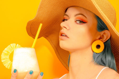 Tropical style photo. Girl with blue hair and sun hat wearing yellow circle earrings handmade by Sophie Filomena. Made in Bristol UK.