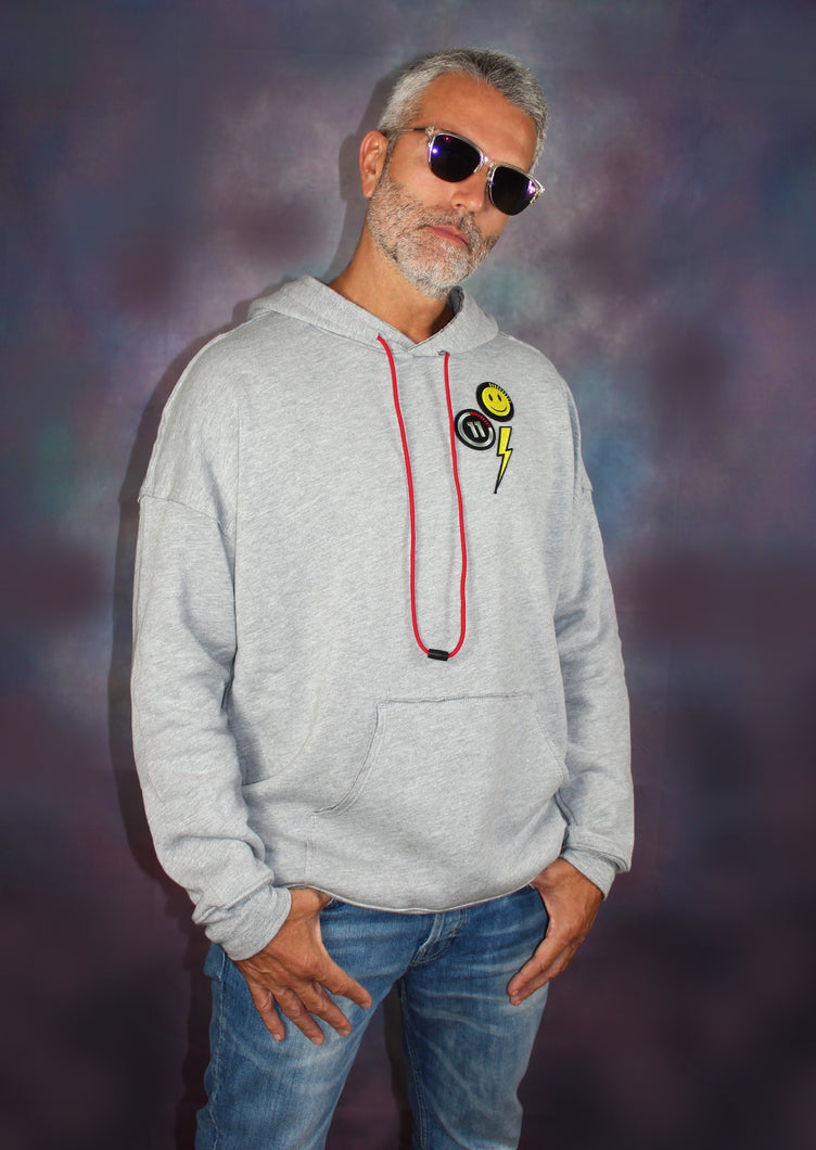 This new happy face grey hoodie offers a casual, relaxed fit for everyday wear.  Oversized fit. Raw seams at shoulders and pocket. Oversized kangaroo pocked.  52% Airlume combed and ring-spun cotton, 48% poly fleece.