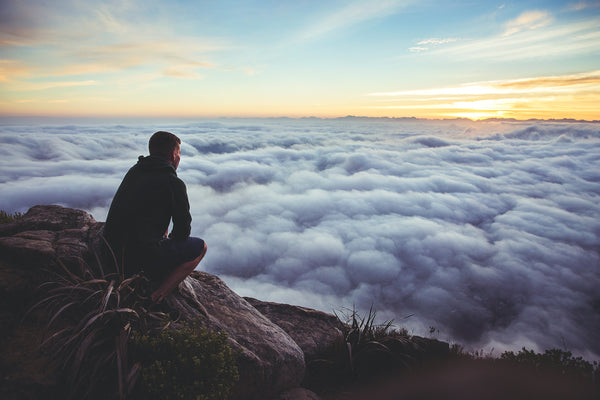 Man on top of mountain, above the clouds; peaceful reflection
