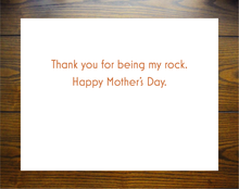 "Load image into Gallery viewer, Art is sky blue and burnt orange red rock colors and depicts the Delicate Arch from Arches National Park along with powerful words, ""graceful,"" ""strong,"" ""serene,"" ""protective,"" ""inspiring,"" ""protective,"" ""supportive,"" and ""wise."" Inside of card reads, ""Thank you for being my rock. Happy Mother's Day."""