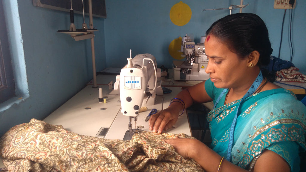 Woman using sewing machine while seated