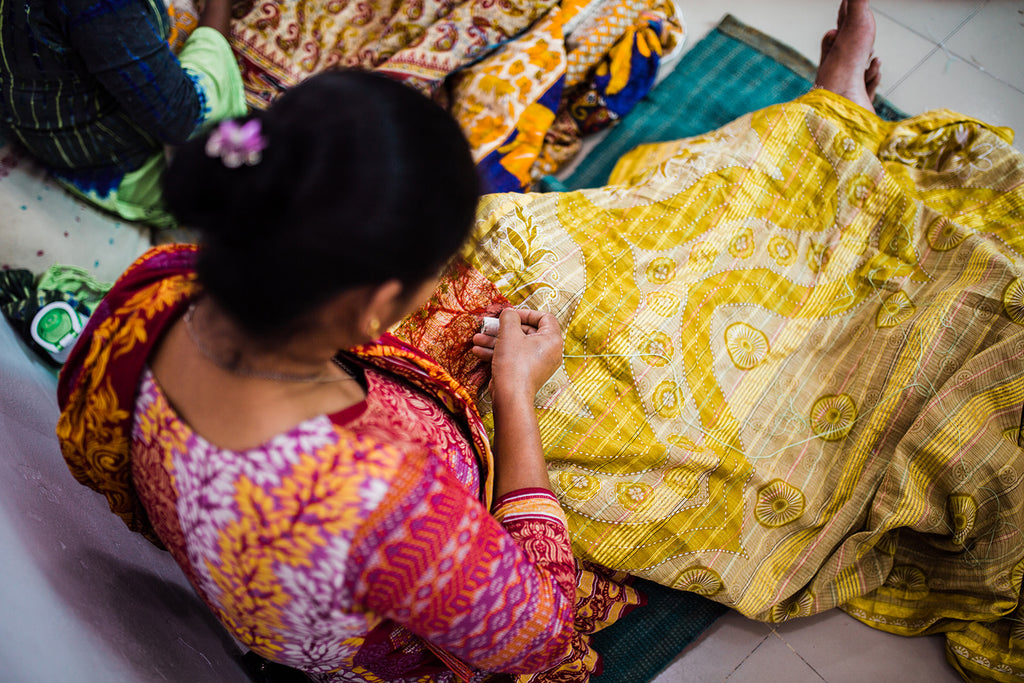 aerial shot of woman sitting and sewing a kantha blanket by hand