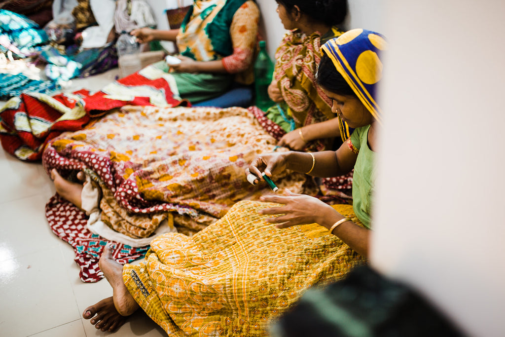 artisan women sewing kantha blankets by hand