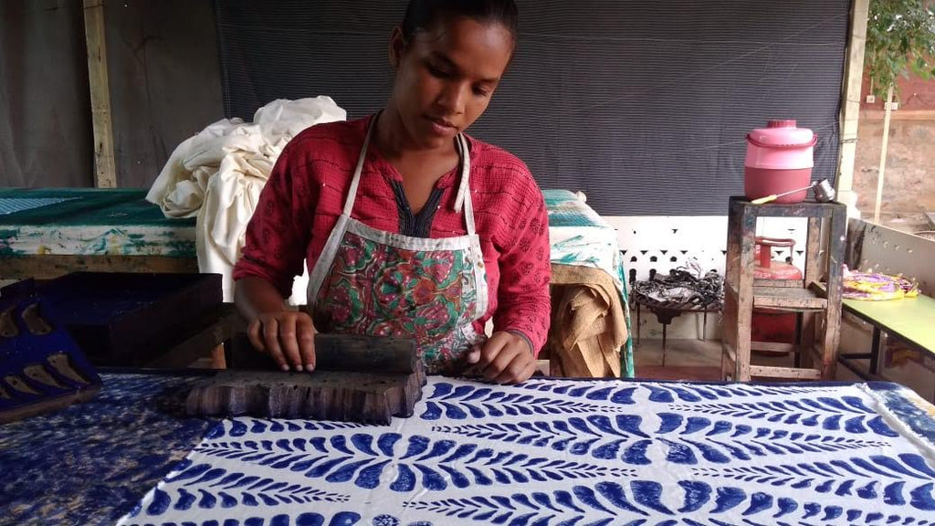 artisan with block printed textiles on table