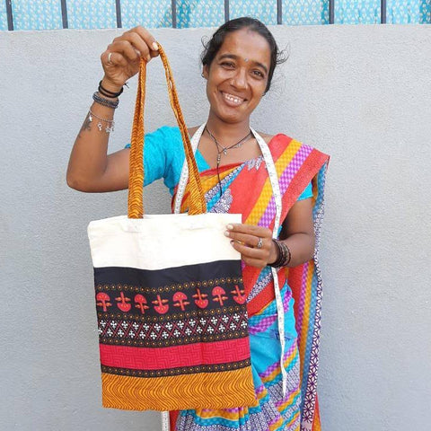 image of a smiling Shakti.ism artisan in Pondicherry, holding up a bright coloured upcycled sari and cotton tote bag