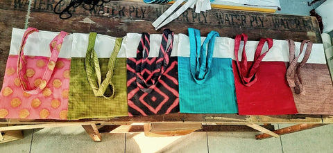 five upcycled sari and cotton tote bags laying flat on a wooden table