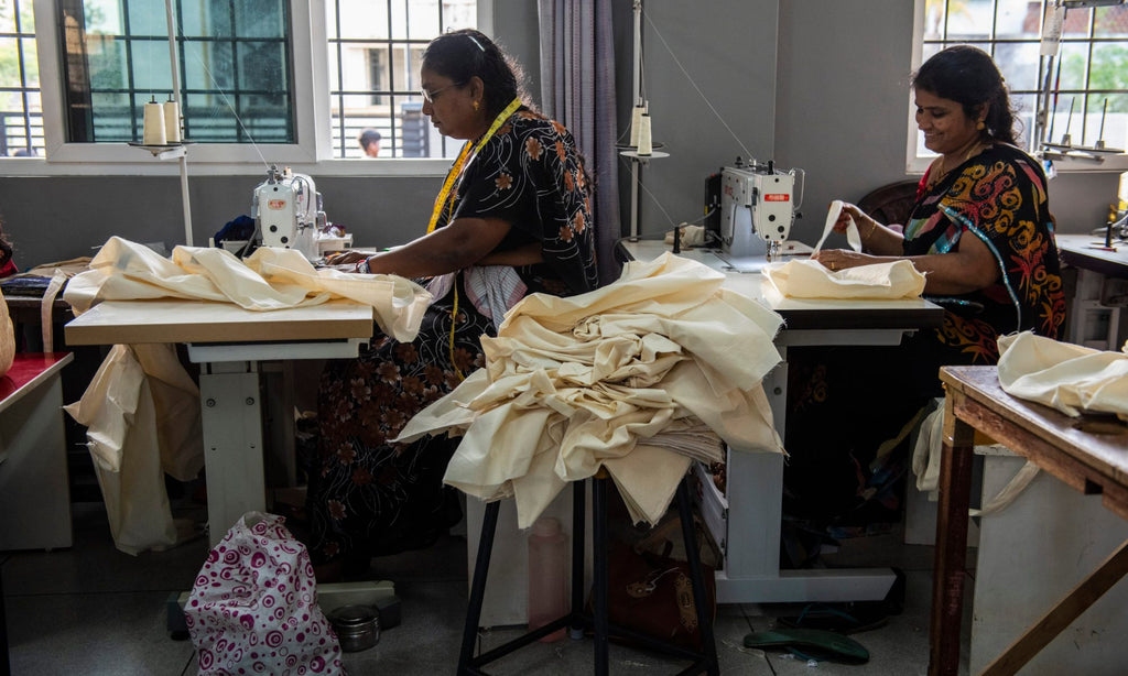two artisan tailors seated at their sewing tables