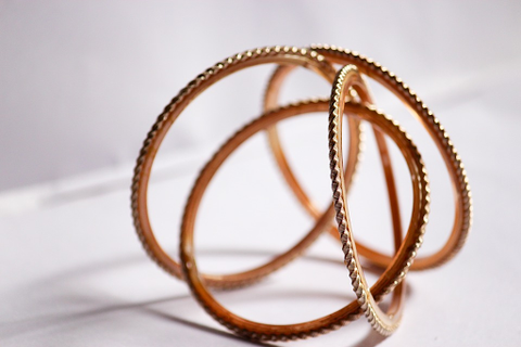 a group of simple rose gold bangles