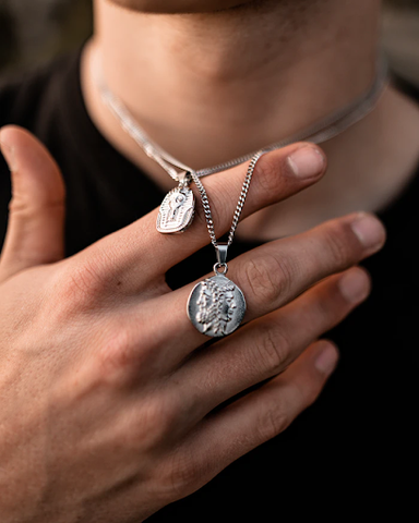 Someone displaying two 925 sterling silver pendant necklaces around their neck.
