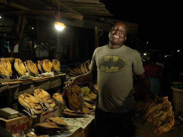 Mr Moyo using a solar light the fish market