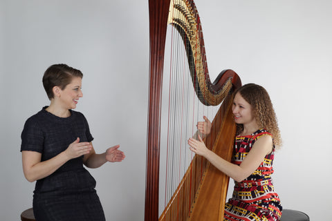 Elizabeth teaching a harp student how to play harp