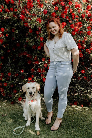 A golden retriever, smiling while wearing a colourful bow tie and green lead. Sitting next to a red haired women, also smiling at the camera. Red bottlebrush background